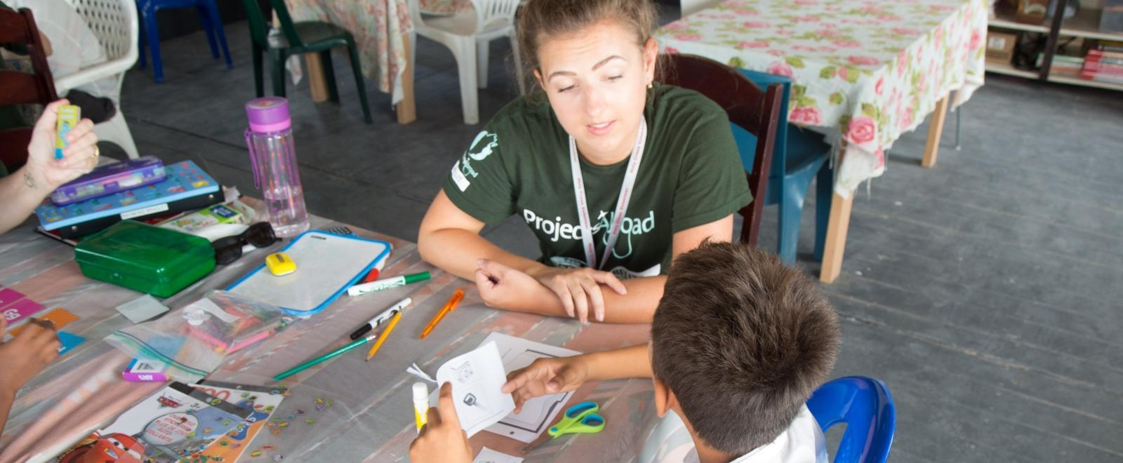 A volunteer helps improve the literacy skills of her students during her teaching work experience in Belize